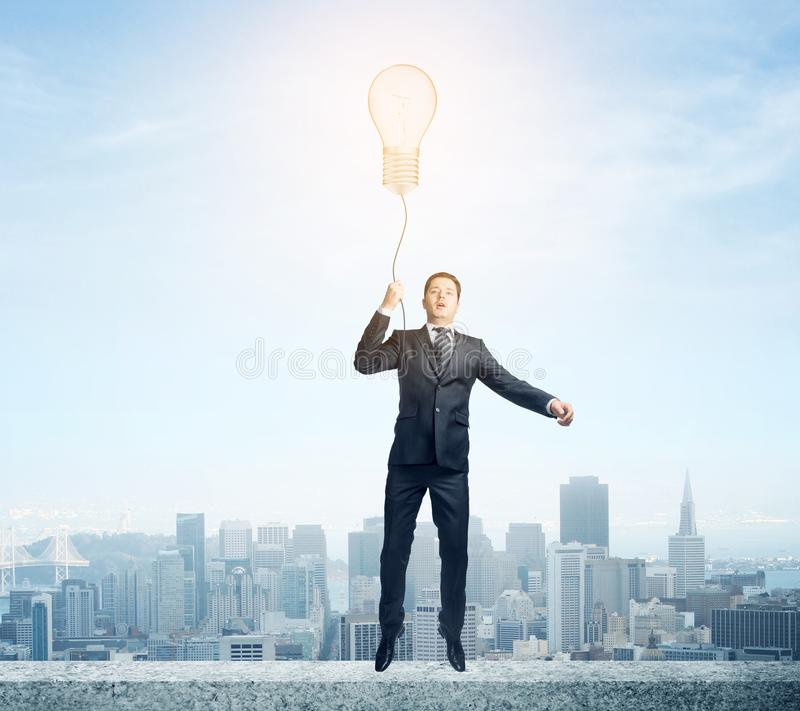 Idea and freedom concept. Businessman flying with abstract glowing lamp balloon on city background. Idea and freedom concept stock photography