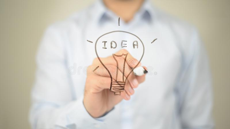Idea, Glowing Bulb Concept, Man writing on transparent screen. High quality stock photography