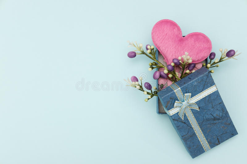 Idea. Heart-shaped pillow and mini flower in gift box on blue background, valentine concept stock image