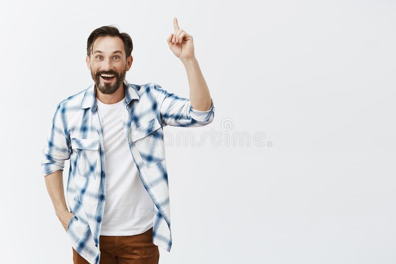 Idea just stroke me, listen. Portrait of thrilled happy good-looking european man in checked shirt over t-shirt, raising stock photography