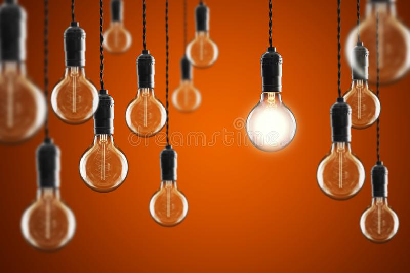Idea and leadership concept Vintage incandescent Edison bulbs on color background. Idea and leadership concept Vintage incandescent Edison type bulbs on color stock images