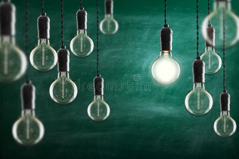Idea and leadership concept Vintage incandescent Edison bulbs on color background. Idea and leadership concept Vintage incandescent Edison type bulbs on color royalty free stock photography