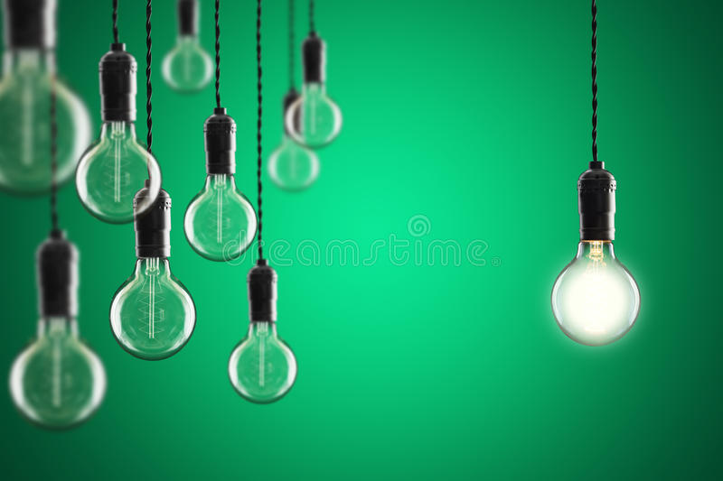 Idea and leadership concept Vintage incandescent Edison bulbs on. Idea and leadership concept Vintage incandescent Edison type bulbs on color wall stock photography