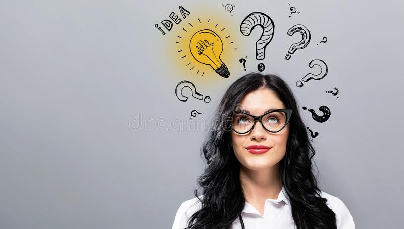 Idea light bulbs with question marks with young businesswoman. In a thoughtful face royalty free stock photography