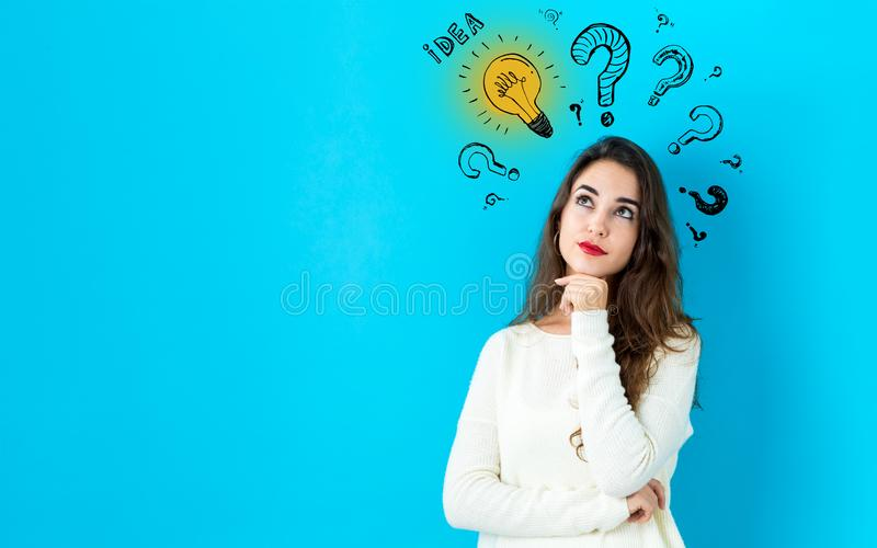 Idea light bulbs with question marks with young woman stock image