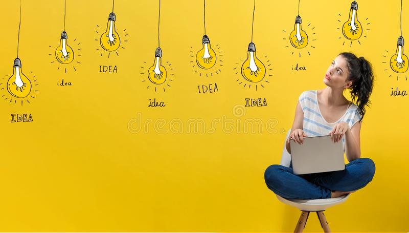Idea light bulbs with woman using a laptop stock photo