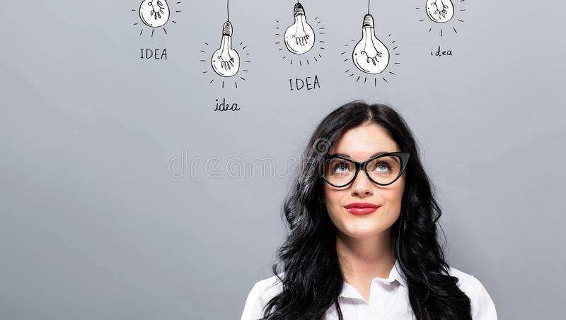 Idea light bulbs with young businesswoman. In a thoughtful face stock photography