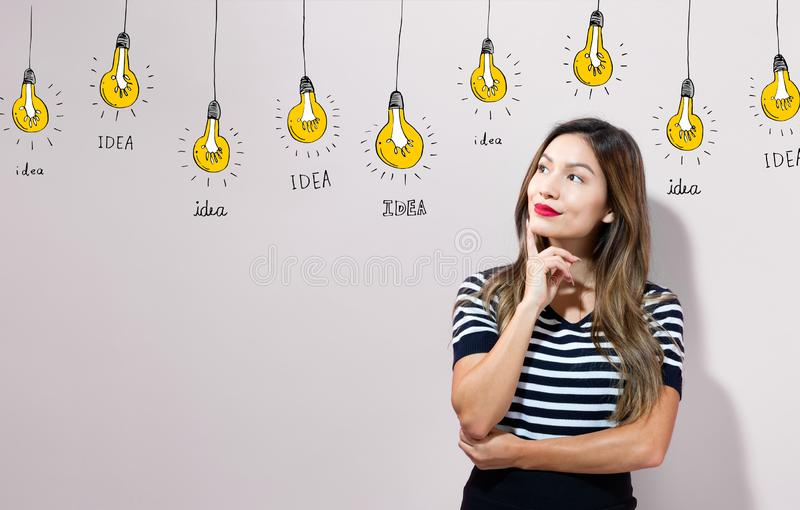 Idea light bulbs with young businesswoman royalty free stock image