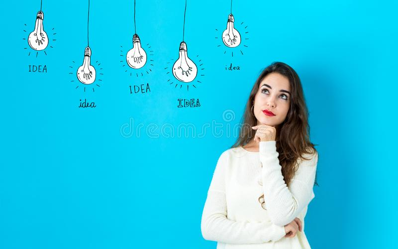 Idea light bulbs with young woman stock photos