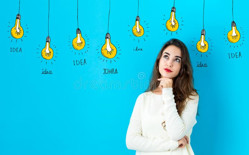 Idea light bulbs with young woman royalty free stock photography