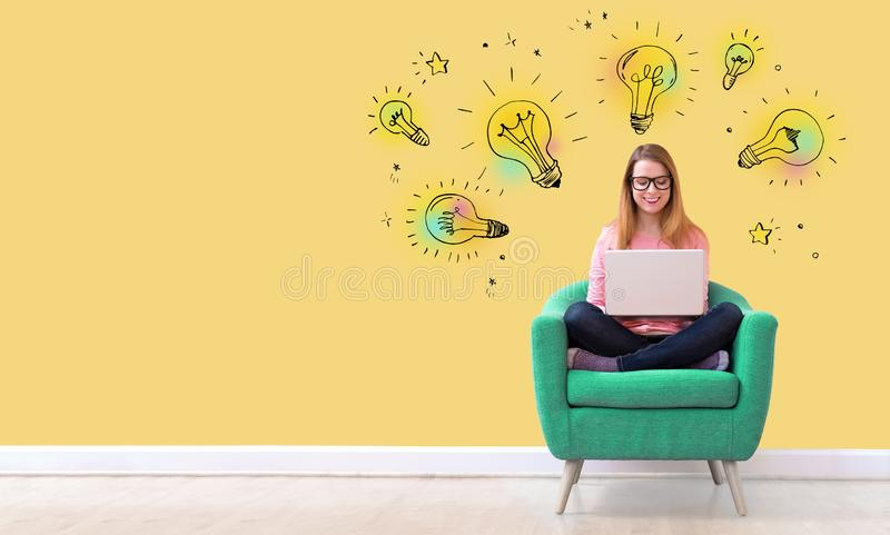 Idea light bulbs with woman using a laptop royalty free stock images