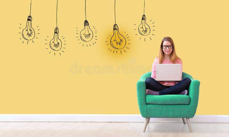 Idea light bulbs with woman using a laptop royalty free stock photo