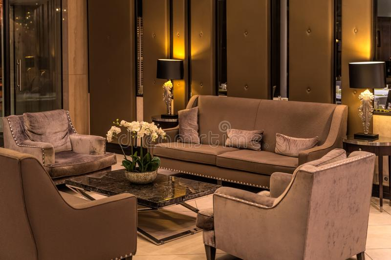 Modern luxurious lobby for hotel with comfortable sofas, arm chairs and moody lighting royalty free stock photos