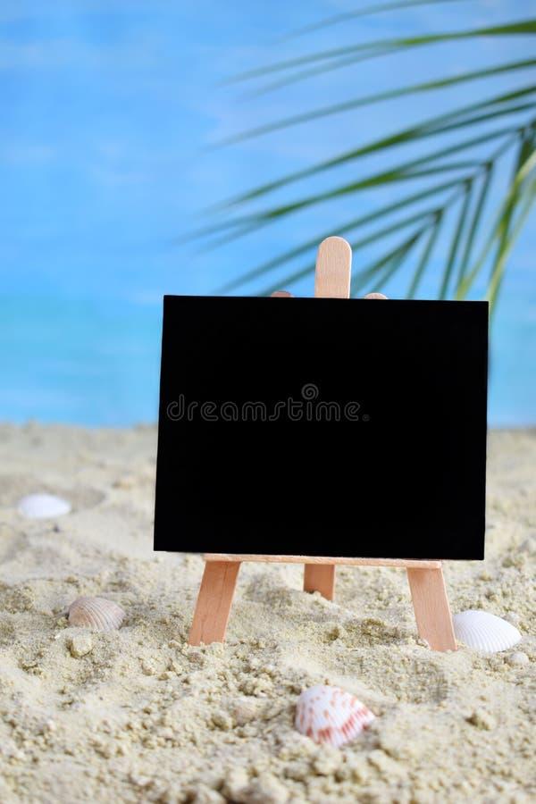 Idea mínima creativa del verano Pizarra en la arena con el mar azul de la falta de definición y la hoja de palma tropical Concept fotografía de archivo