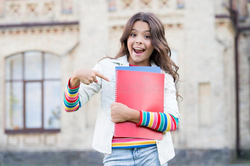 The idea made in book. Happy small child pointing finger at book with genius idea. Adorable schoolgirl got main idea of stock photos