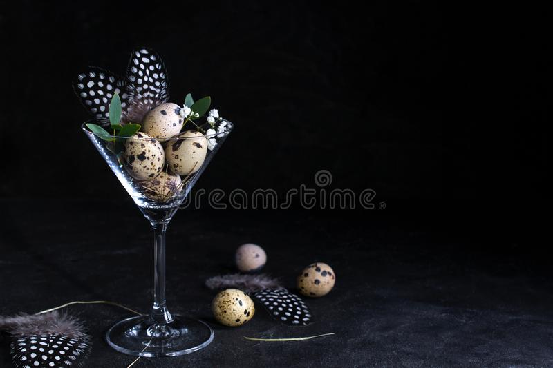 Idea of modern easter interior decoration. Quail eggs in cocktail glass on dark rusty background. Copyspace stock photo