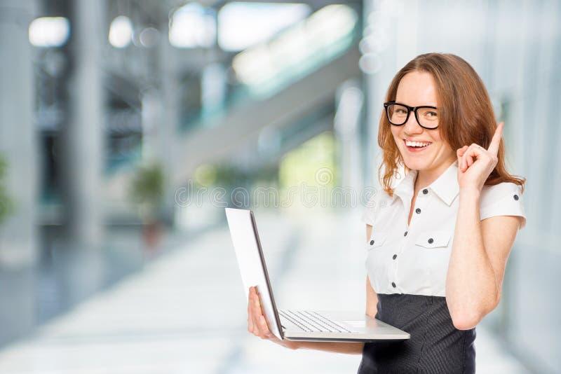 idea! Ragazza in vestiti dell'ufficio con un computer portatile immagine stock
