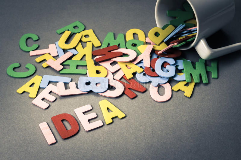 Idea spill. Wood letters spill out of the cup as Idea stock photography