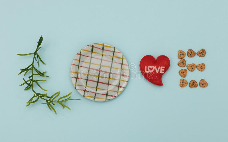 Idea. Words of love from leaves, dish, mini heart shape and wooden button on blue background, Valentine concept royalty free stock images