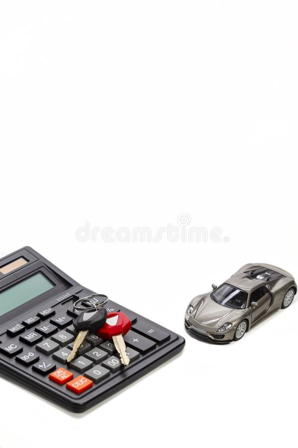 Ideas of Cars Loans and Credits. Composition of Scale Car and Keys against Calculator on Background. Vertical Image Orientation stock photos