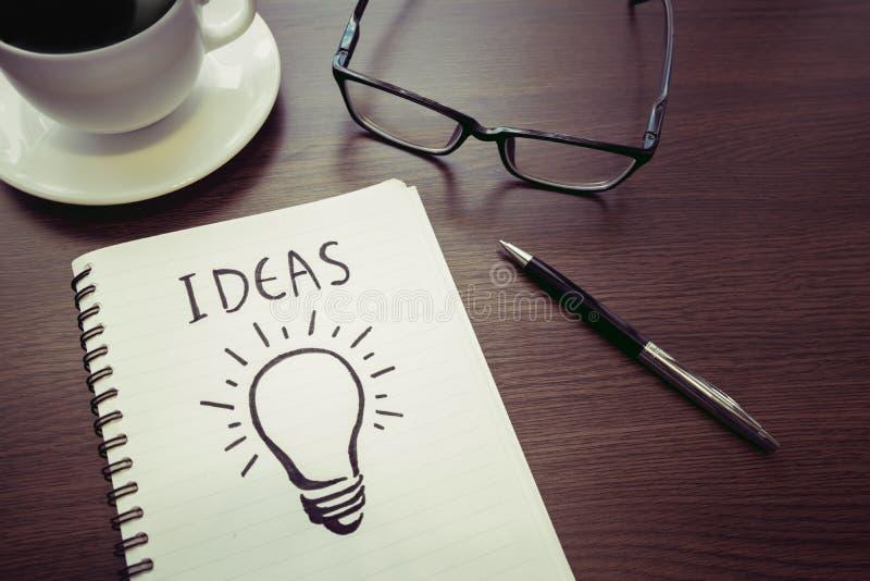 Ideas de los conceptos de la creatividad del negocio dibujo de la bombilla en la libreta foto de archivo libre de regalías