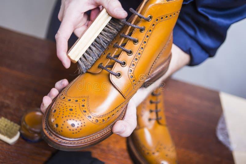 Ideas del calzado Primer de las manos masculinas de la limpieza con la escobilla imagen de archivo