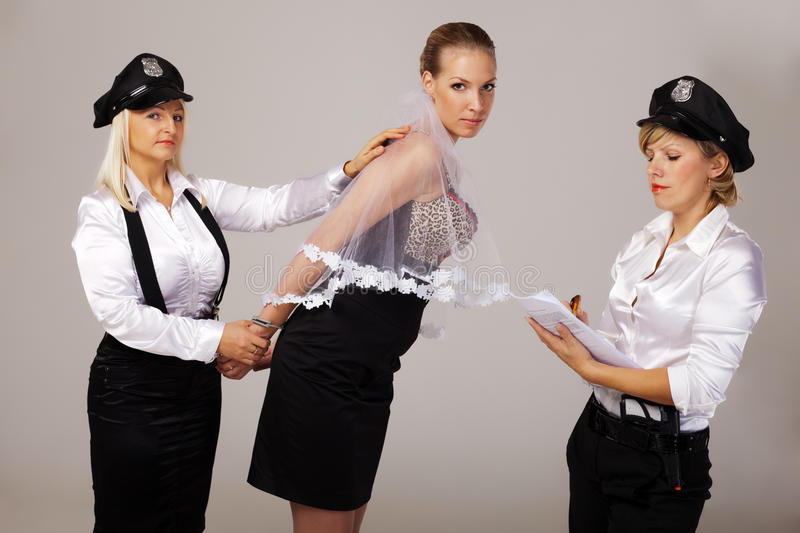 Ideas for hen party: take fiancée under arrest. Hen party mates are taking fiancée under arrest stock image
