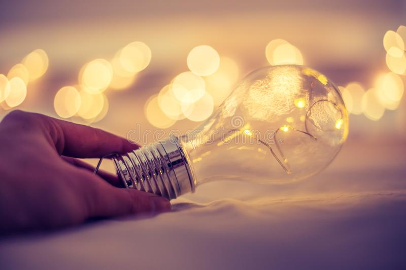 Ideas and innovation: Light bulb with LEDs is lying in the bed, hands touching. Spot lights in the blurry background. LED light bulb is lying in the bed, hands stock images