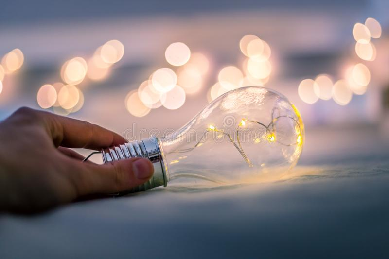 Ideas and innovation: Light bulb with LEDs is lying in the bed, hands touching. Spot lights in the blurry background. LED light bulb is lying in the bed, hands royalty free stock images