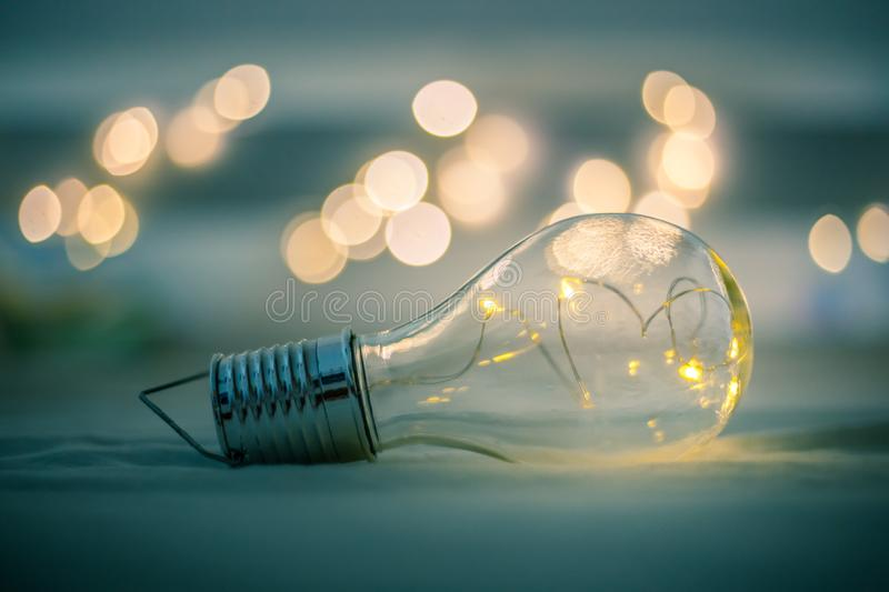 Ideas and innovation: Light bulb with LEDs is lying in the bed. Spot lights in the blurry background. LED light bulb is lying in the bed. Symbol for ideas and royalty free stock image