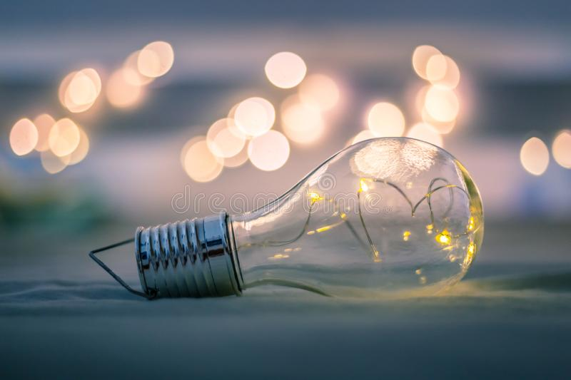 Ideas and innovation: Light bulb with LEDs is lying in the bed. Spot lights in the blurry background. LED light bulb is lying in the bed. Symbol for ideas and stock photography