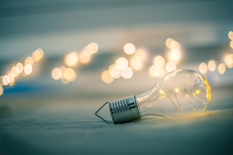 Ideas and innovation: Light bulb with LEDs is lying in the bed. Spot lights in the blurry background. LED light bulb is lying in the bed. Symbol for ideas and royalty free stock photos