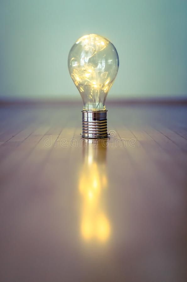Ideas and innovation: Light bulb with LEDs is lying on the wooden floor. Copy space. LED light bulb is lying on the wooden floor. Symbol for ideas and innovation royalty free stock photo