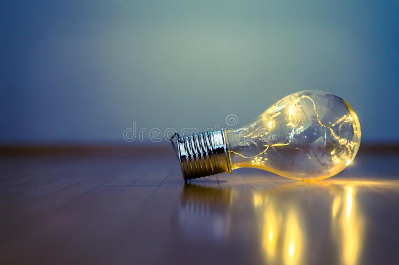 Ideas and innovation: Light bulb with LEDs is lying on the wooden floor. Copy space. LED light bulb is lying on the wooden floor. Symbol for ideas and innovation royalty free stock image