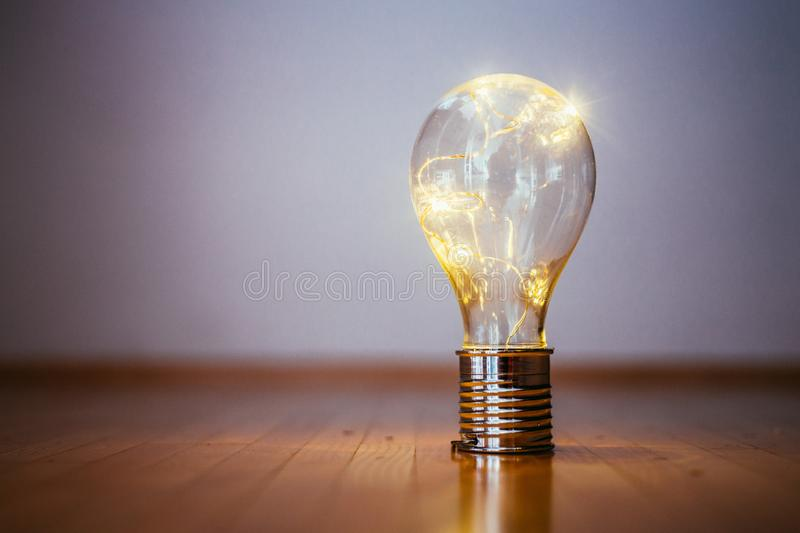 Ideas and innovation: Light bulb with LEDs is lying on the wooden floor. Copy space. LED light bulb is lying on the wooden floor. Symbol for ideas and innovation royalty free stock photography