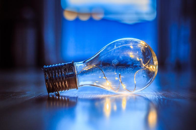 Ideas and innovation: Light bulb with LEDs is lying on the wooden floor. Window and light in the blurry background stock illustration