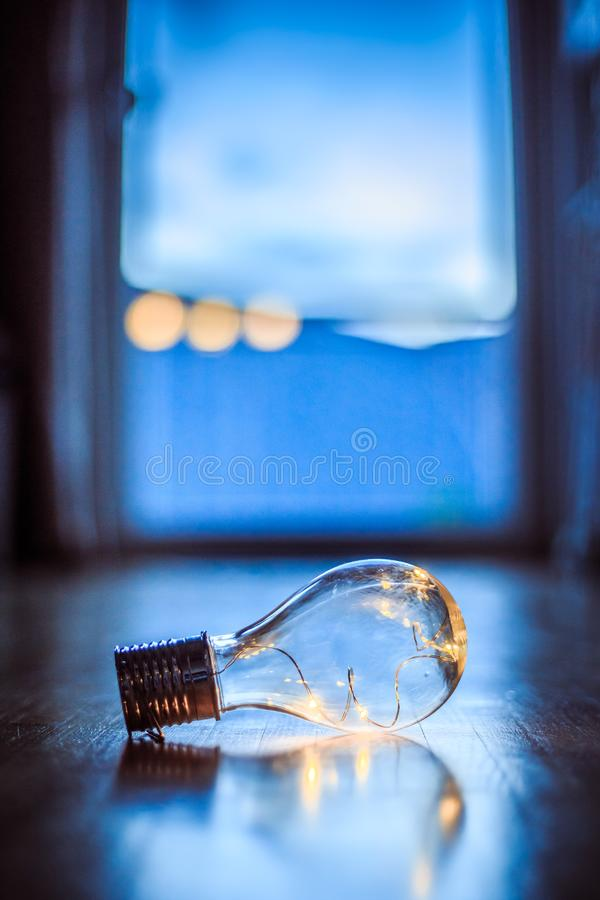 Ideas and innovation: Light bulb with LEDs is lying on the wooden floor. Window and light in the blurry background vector illustration