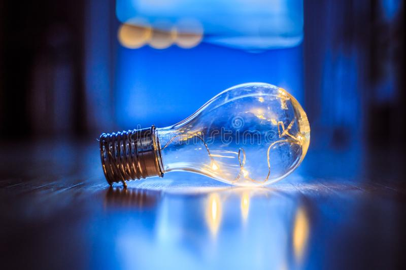 Ideas and innovation: Light bulb with LEDs is lying on the wooden floor. Window and light in the blurry background. LED light bulb is lying on the wooden floor stock photo
