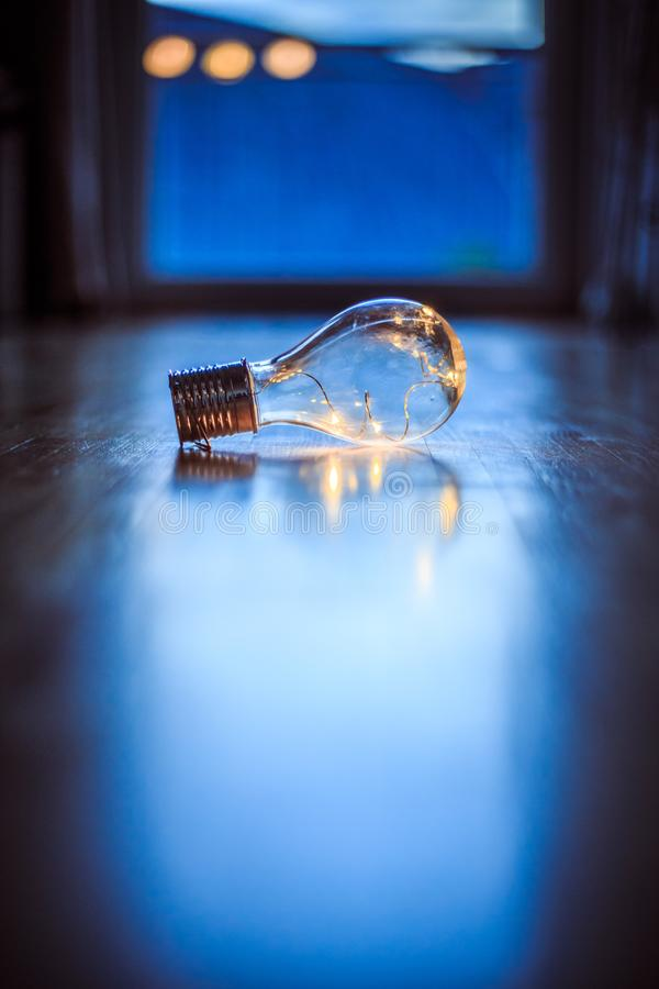 Ideas and innovation: Light bulb with LEDs is lying on the wooden floor. Window and light in the blurry background. LED light bulb is lying on the wooden floor stock photos