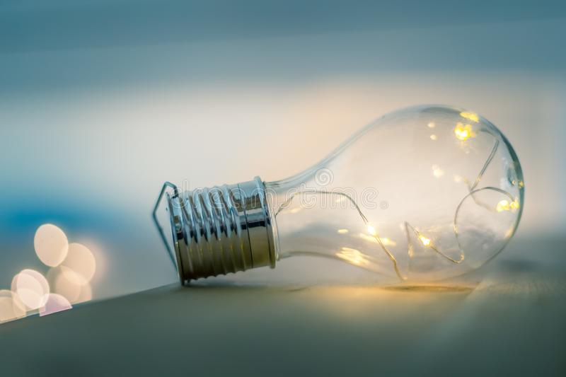 Ideas and innovation: Light bulb with LEDs is lying on a wooden table. Spot lights in the blurry background. LED light bulb is lying on a wooden table. Symbol royalty free stock image