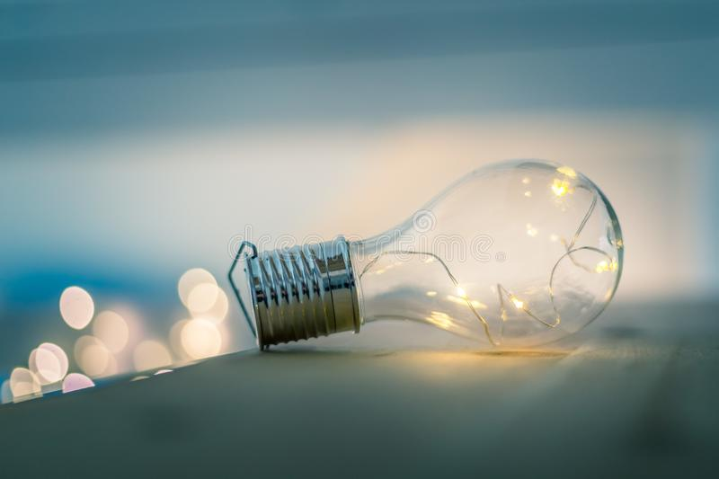 Ideas and innovation: Light bulb with LEDs is lying on a wooden table. Spot lights in the blurry background. LED light bulb is lying on a wooden table. Symbol stock photos