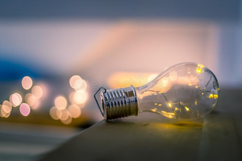 Ideas and innovation: Light bulb with LEDs is lying on a wooden table. Spot lights in the blurry background. LED light bulb is lying on a wooden table. Symbol stock image