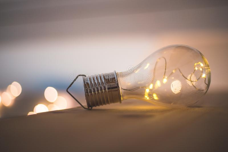 Ideas and innovation: Light bulb with LEDs is lying on a wooden table. Spot lights in the blurry background. LED light bulb is lying on a wooden table. Symbol royalty free stock photography