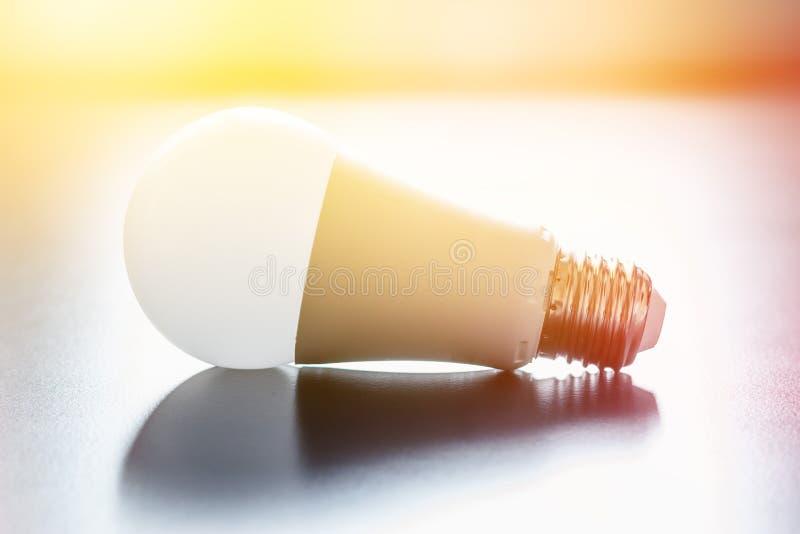 Ideas and innovation: light bulb lying on a desk. Sunlight. White light bulb lying on a desk, concept for ideas. Sunlight innovation power technology object royalty free stock photos
