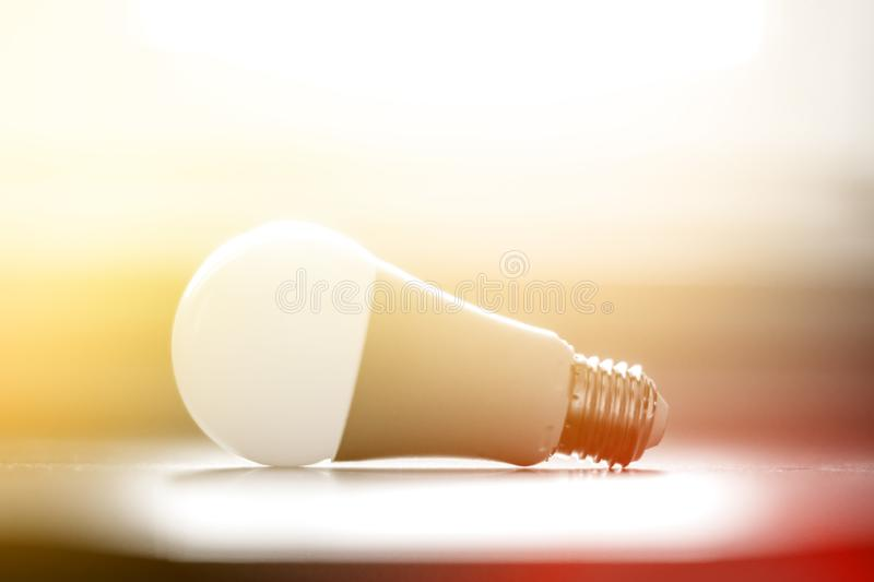 Ideas and innovation: light bulb lying on a desk. Sunlight. White light bulb lying on a desk, concept for ideas. Sunlight innovation power technology object stock images