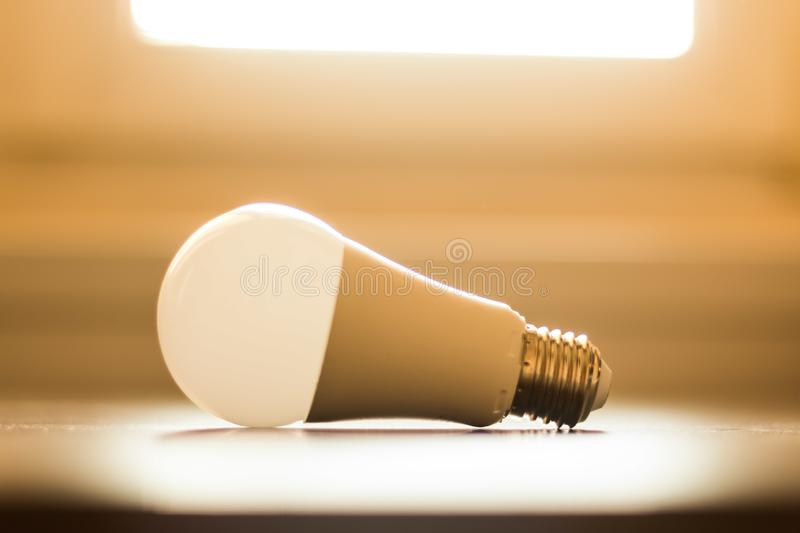 Ideas and innovation: light bulb lying on a desk. Sunlight. White light bulb lying on a desk, concept for ideas. Sunlight innovation power technology object royalty free stock photo