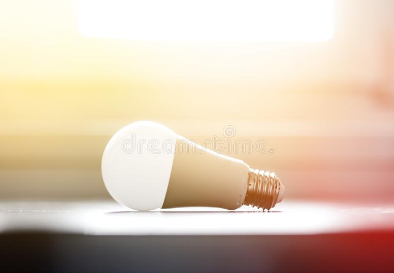 Ideas and innovation: light bulb lying on a desk. Sunlight. White light bulb lying on a desk, concept for ideas. Sunlight innovation power technology object royalty free stock image