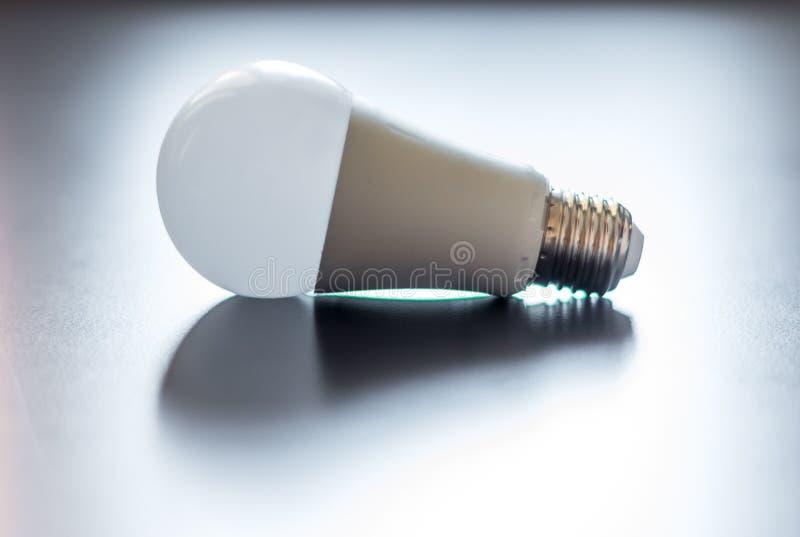 Ideas and innovation: light bulb lying on a desk. White light bulb lying on a desk, concept for ideas innovation power technology object creativity creativeness stock photography