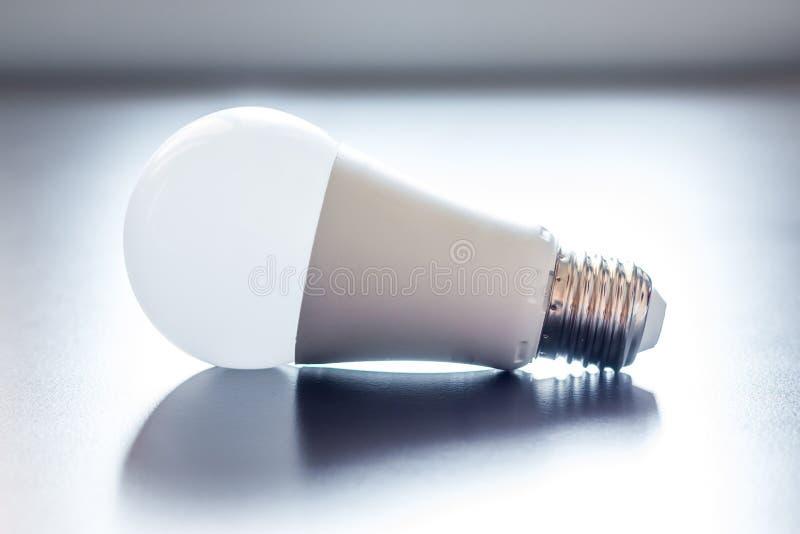 Ideas and innovation: light bulb lying on a desk. White light bulb lying on a desk, concept for ideas innovation power technology object creativity creativeness royalty free stock photography