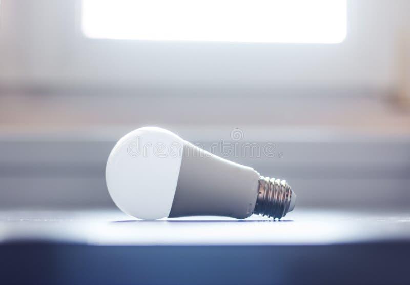 Ideas and innovation: light bulb lying on a desk. White light bulb lying on a desk, concept for ideas innovation power technology object creativity creativeness stock photo